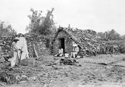 Indígenas desgranan maíz junto a una vivienda
