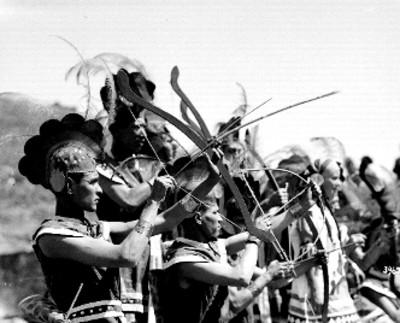Danzantes indígenas con arcos durante fiesta, retrato de grupo