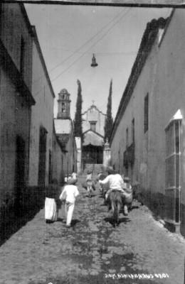 Hombres y mujer indígenas con asnos en una calle