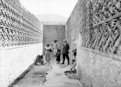 Familia indígena junto a hombre en un corredor de las ruinas de Mitla