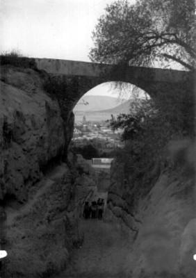 Hombres indígenas caminan bajo el acueducto, al fondo el poblado