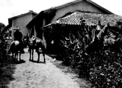 Indígena con caballos frente a una vivienda