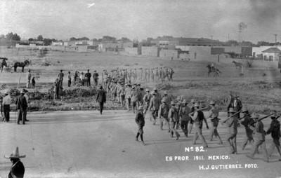 Revolucionarios portan armas y marchan alineados en explanada