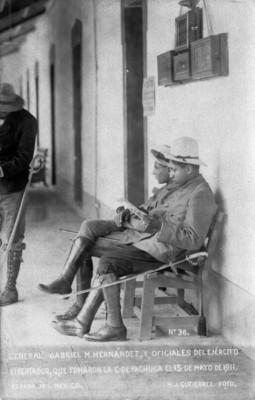 """""""General Gabriel M. Hernández y oficiales del ejército libertador"""" sentados en una banca"""