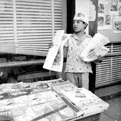 Voceador con periódicos junto a un puesto de revistas