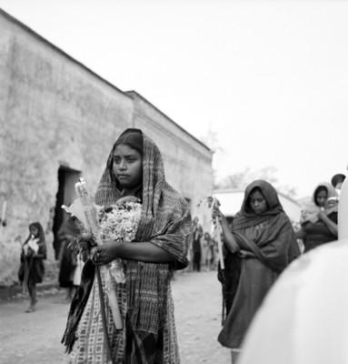 Mujeres con velas y flores caminan por una calle durante un sepelio
