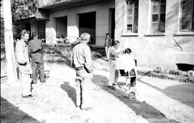 Peluquero corta el cabello a anciano en un jardín del Hospital General