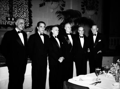 Carlos Contreras reunido con varios hombres en un salón durante un eventos social, retrato de grupo
