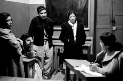 Trabajadora social conversa con mujeres y anciano en una reunión
