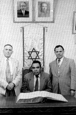 Judios ante una mesa con una biblia, retrato de grupo