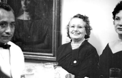 Mesero ofrece bebidas a mujeres en una exposición de arte