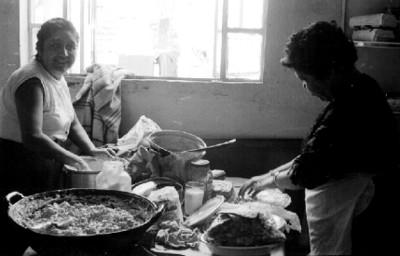 Mujer lava trastos en una cocina