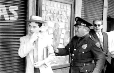 Policía sujeta a maestro durante una manifestación