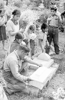 Hombre deposita el ataúd de un niño sobre una tumba
