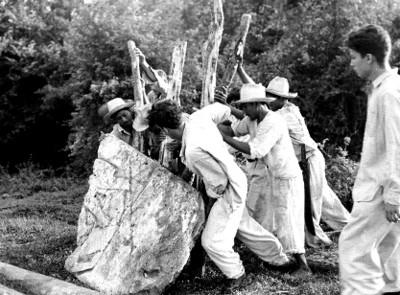 Arqueólogos y trabajadores levantan una estela durante una expedición