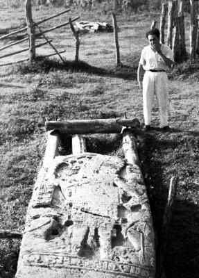 Arqueólogo observa una estela sobre el pasto