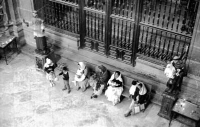 Mujeres y niños descansan en el atrio de la Catedral
