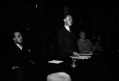 Luis Chico Goerne escucha las palabras de un hombre durante una ceremonia en un salón