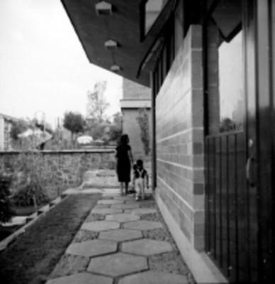 Mujer y niño caminan hacia su casa