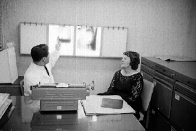 Médico muestra radiografías a mujer en un consultorio
