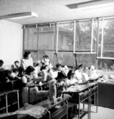 Alumnos realizan trabajos manuales en un aula