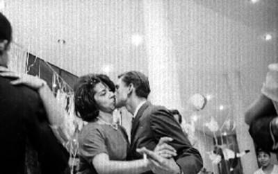 Pareja se besa durante una fiesta