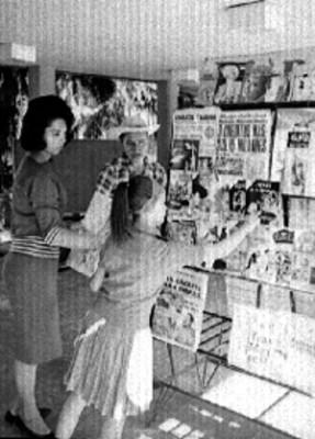 Mujer e hija en puesto de periódicos