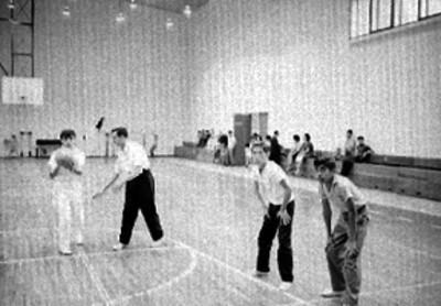 Adolescentes entrenan básquetbol en un gimnasio