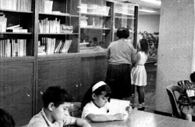 Niños leen en una biblioteca