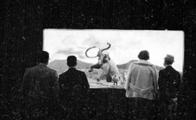 Gente observa una pintura de la caza del mamut