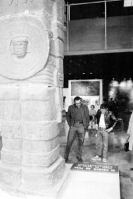 Hombres observan la placa de un atlante de Tula