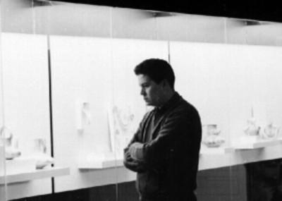 Hombre observa exposición de cerámica prehispánica