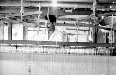 Artesanos tejen en un telar manual