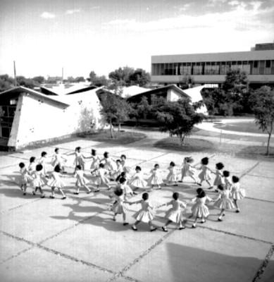 Niñas juegan ronda infantil en el patio de una escuela