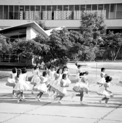 Niñas juegan una ronda en el patio de una escuela