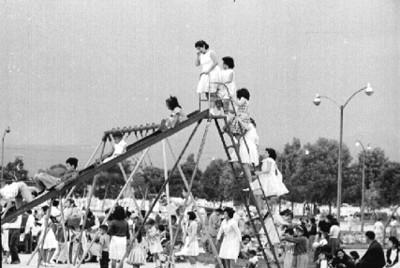 Niñas juegan en la resbaladilla de un parque