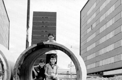 Niños juegan en unos tubos de drenaje