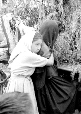 Niña abraza a mujer durante representación de la Pasión de Cristo