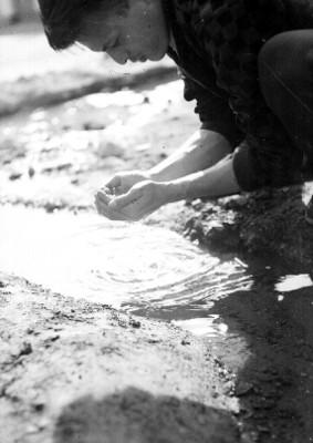 Manos recogen agua de un arroyo
