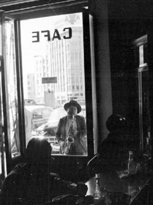 Músico toca el saxofón afuera de una cafetería