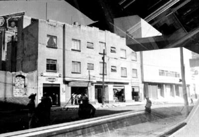 Gente y edificio en una calle de la ciudad de México, vista através de una ventana