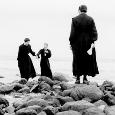 Monjas sentadas sobre rocas a la orilla del mar