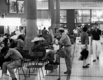 Trabajador de limpieza y gente en la terminal de autobúses de Guadalajara