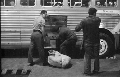 Pasajeros suben equipaje a autobús en la terminal