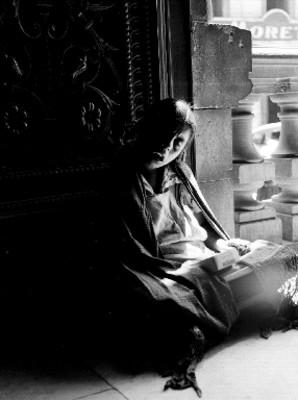 Mujer sentada junto a una puerta con caja de chicles