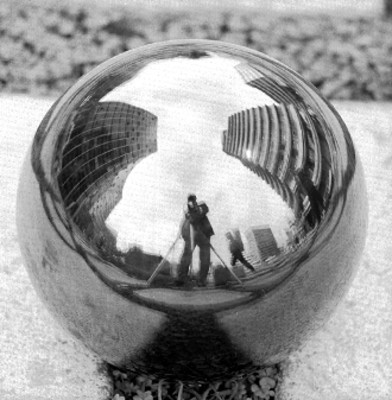 Mano sostiene esfera con reflejos de la ciudad
