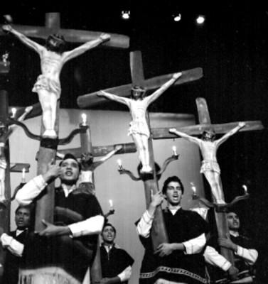 Bailarines con cristos durante la presentación de un baile