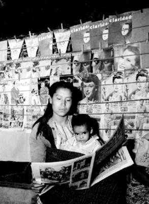 Mujer y niño leen periódicos junto a puesto de revistas