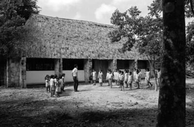 Hombre rodeado de niñas en una escuela