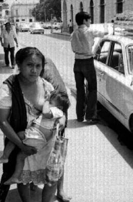 Mujer indígena amamanta a bebe en una calle